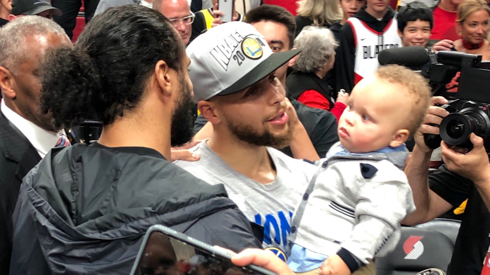 Warriors' Stephen Curry celebrates with his son after sweeping the Trail Blazers