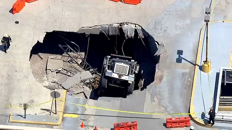 Dump truck falls through upper level of parking garage in New Jersey