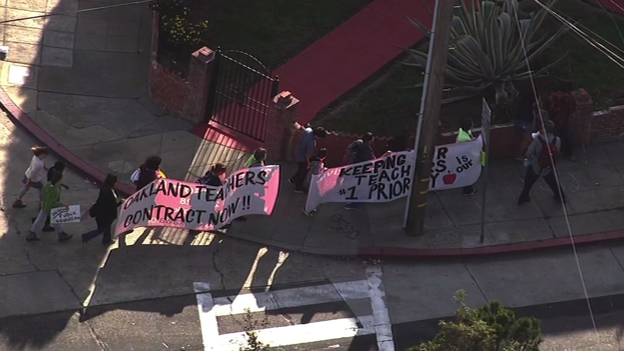 Teachers marching with protest signs