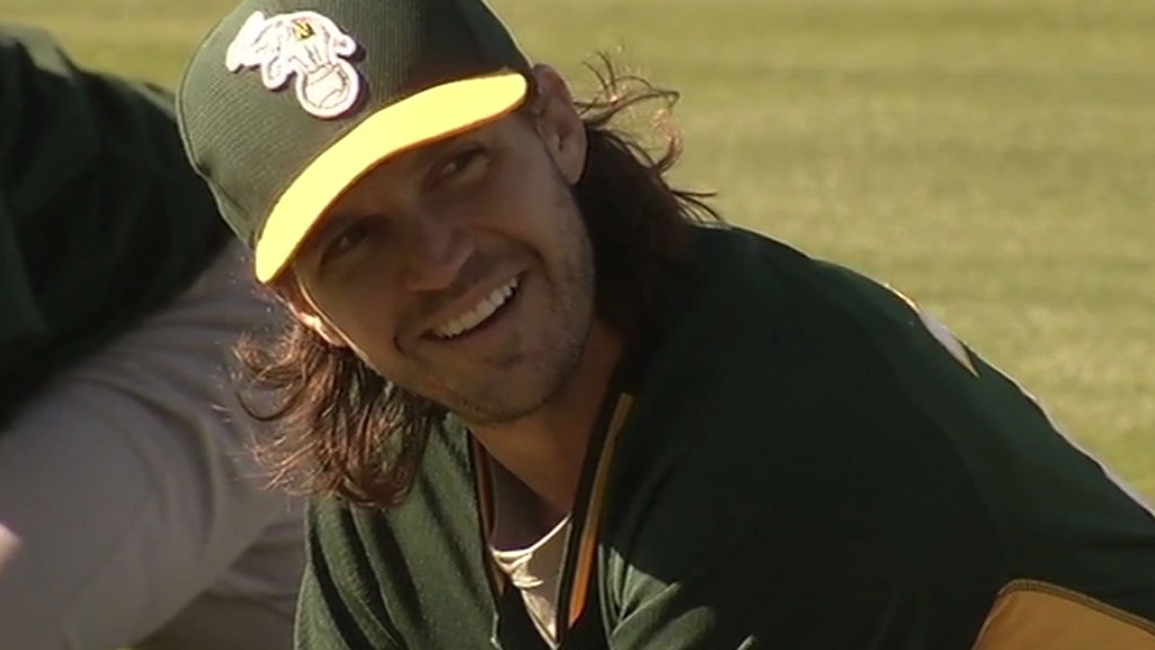 Barry Zito smiles while stretching on the field during spring training