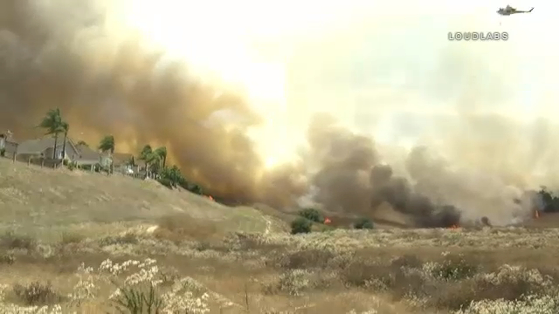 A multi-acre brush fire was burning in Chino Hills Sunday afternoon, possibly threatening nearby homes.