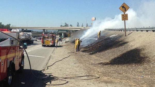 Firefighters work to put out a brush fire on the side of the westbound 210 Freeway near in Irwindale on Sunday, March 8, 2015.
