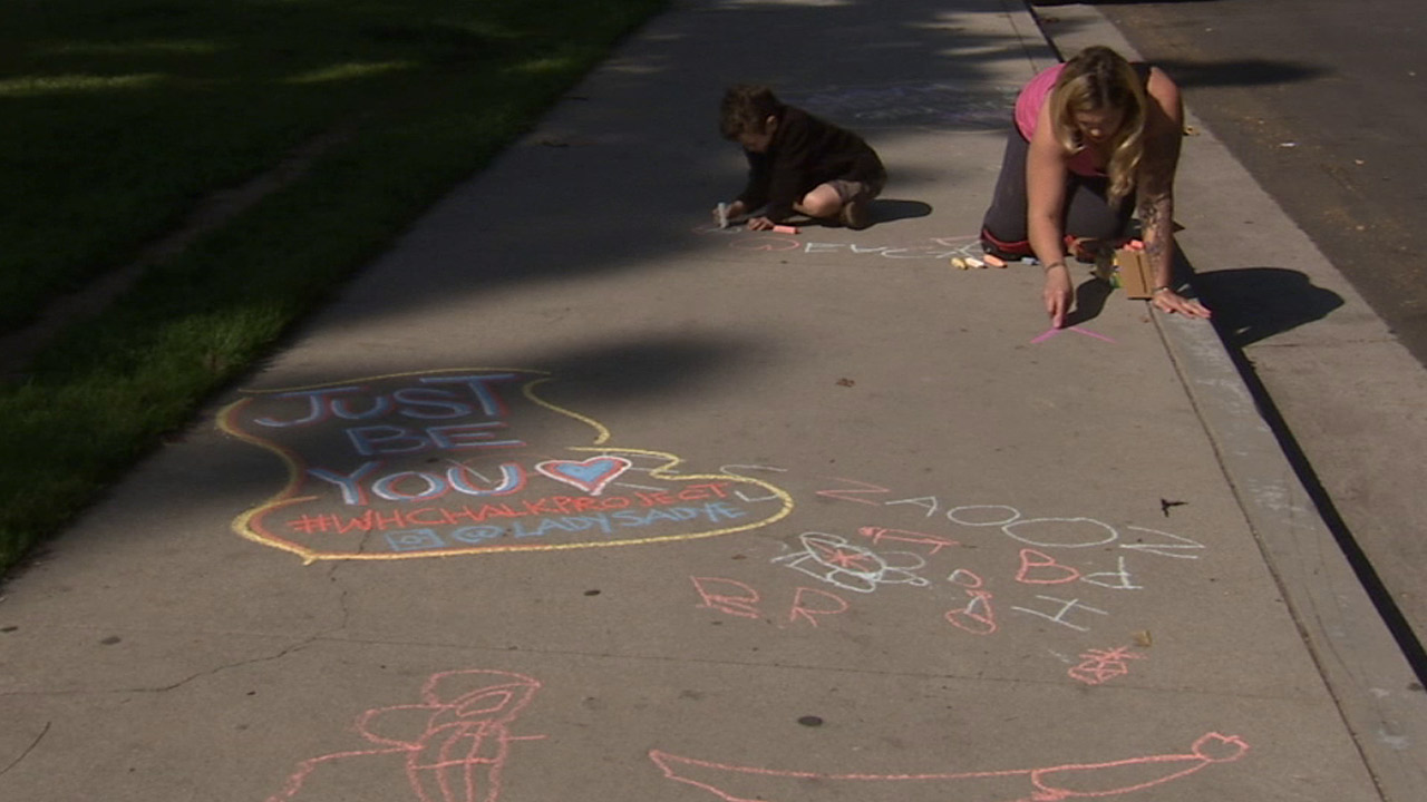 Sadye Davenport and her son, Indigo, create inspiring and colorful chalk art messages on a sidewalk as a way to bring joy to people in Woodland Hills.
