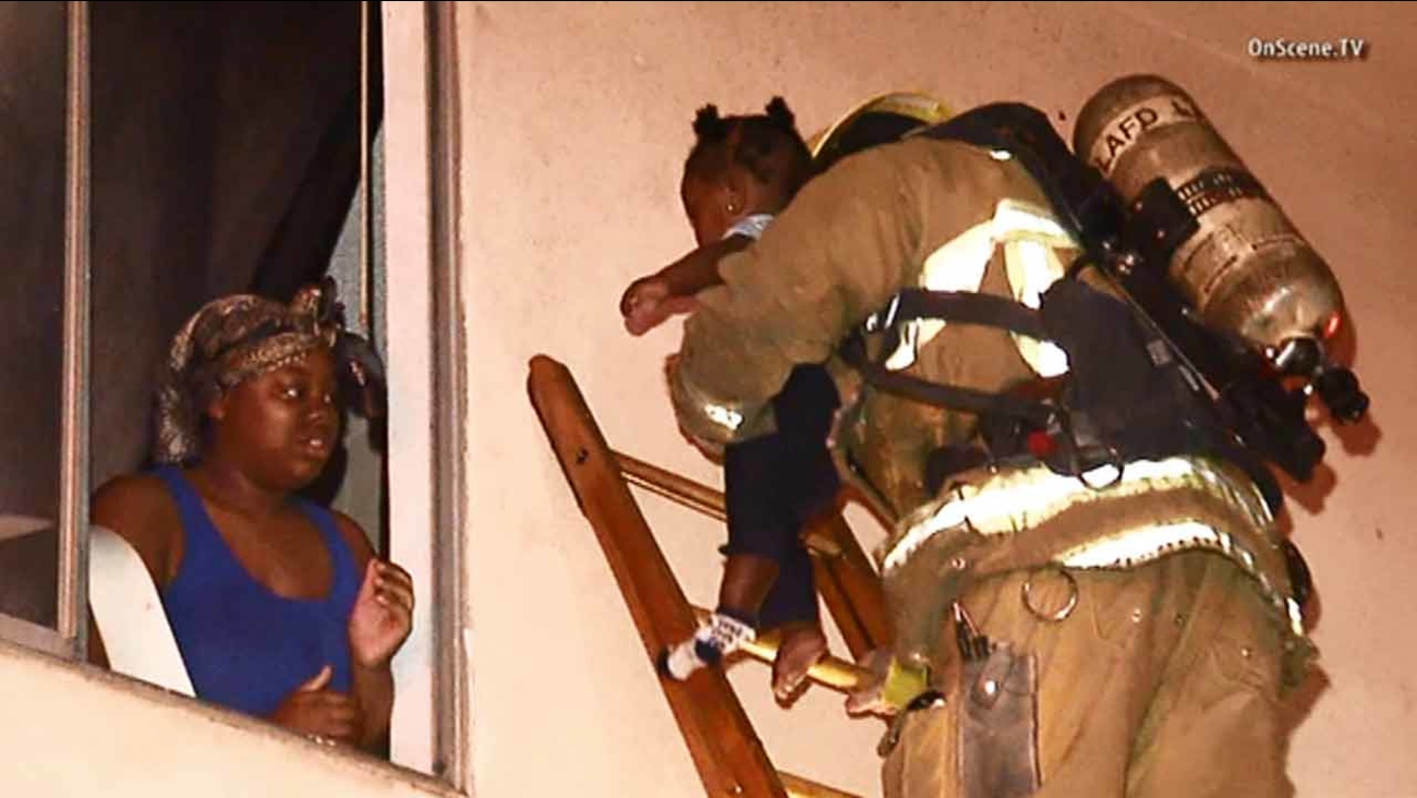 A woman hands off a child to a firefighter during a fire in a South Los Angeles apartment complex on Monday, March 9, 2015.