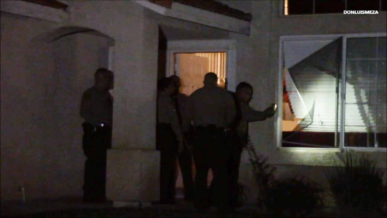 Law enforcement officials investigate the scene of a residential burglary in Palmdale on Wednesday, March 11, 2015.