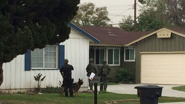 SWAT officers go door to door in the neighborhood to talk to residents following a stabbing in the area on Wednesday, March 11, 2015.