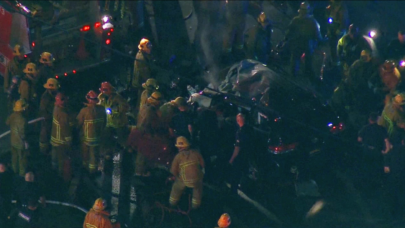Los Angeles firefighters and police officers work to extract two suspects from a car, which crashed into the back of a fire truck after a short pursuit on Wednesday, March 11, 2015