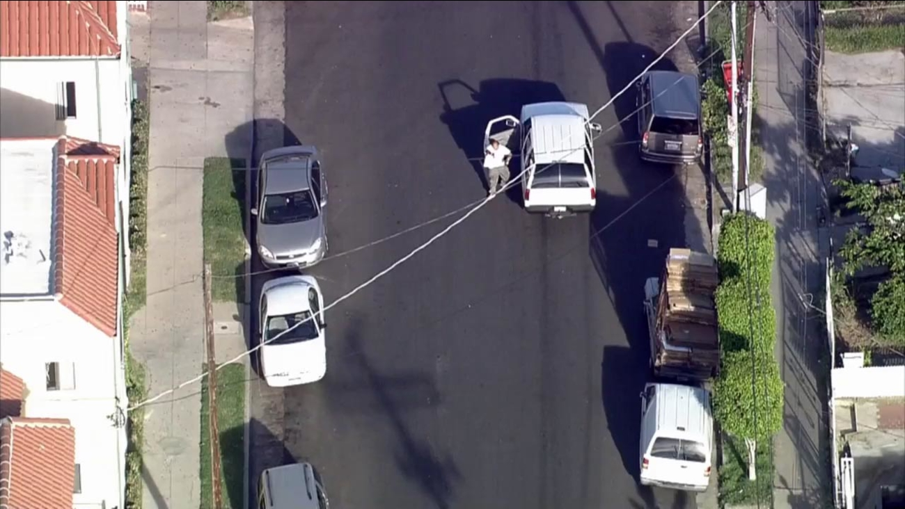 A suspect is seen pointing a weapon at L.A. County sheriff's deputies in South L.A. at the end of a chase on Friday, March 13, 2015.