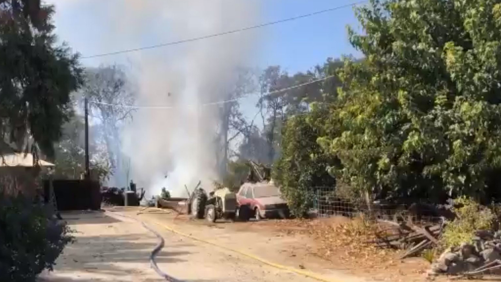 Firefighters battle grass fire threatening structure in Fresno County