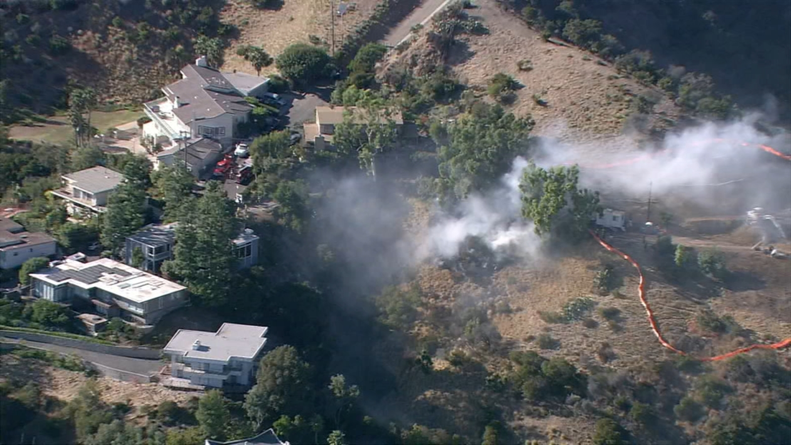 Firefighters battle small brush fire burning near homes in Brentwood