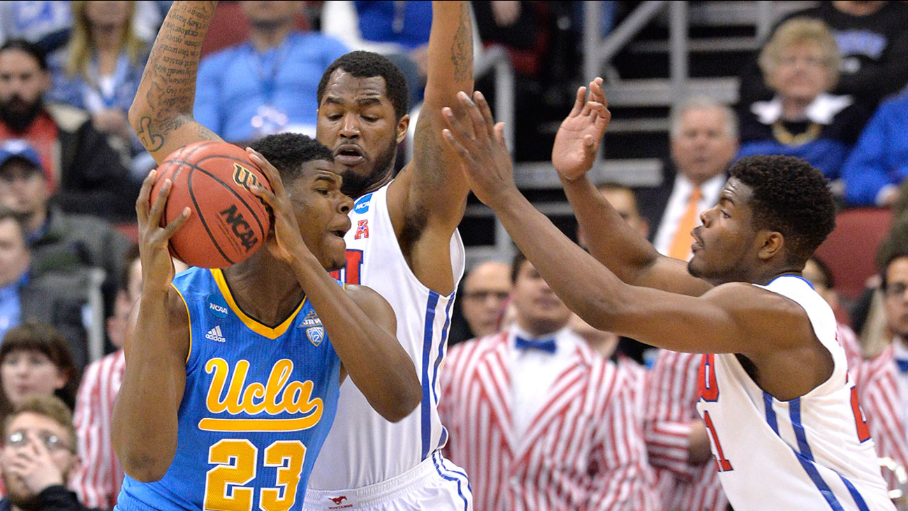UCLA's Tony Parker, left, looks for an opening against SMU's Ben Emelogu, right, and Markus Kennedy during the second round of the NCAA college basketball tournament in Louisville, Ky., Thursday, March 19, 2015.