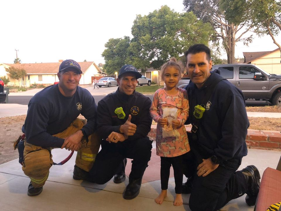 The Ventura County Fire Department shows a smiling birthday girl posing with four of her father's colleagues
