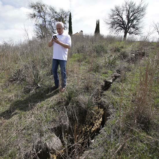 """<div class=""""meta image-caption""""><div class=""""origin-logo origin-image none""""><span>none</span></div><span class=""""caption-text"""">Steve Mellgren takes a business phone call along a fissure that is opening in the ground next to his home at Lake Whitney March 17, 2015, in Whitney, Texas. . (AP Photo/ LM Otero)</span></div>"""