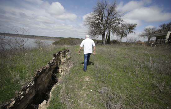 """<div class=""""meta image-caption""""><div class=""""origin-logo origin-image none""""><span>none</span></div><span class=""""caption-text"""">Steve Mellgren walks along a fissure that is opening on the cliff next to his home at Lake Whitney March 17, 2015, in Whitney, Texas. (AP Photo/ LM Otero)</span></div>"""