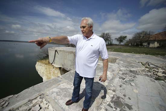 """<div class=""""meta image-caption""""><div class=""""origin-logo origin-image none""""><span>none</span></div><span class=""""caption-text"""">Steve Mellgren points out the cliff that collapsed and that ultimately caused the destruction of the house next to his home at Lake Whitney (AP Photo/ LM Otero)</span></div>"""