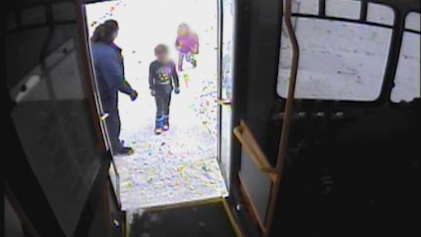 Two small children not properly dressed for the snow being rescued by a bus driver