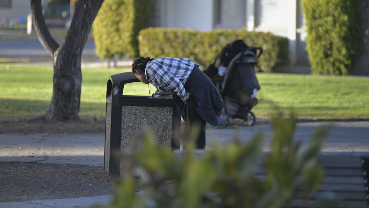 A person reaches into a garbage can in Fremont, Calif.