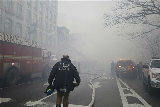 "<div class=""meta image-caption""><div class=""origin-logo origin-image none""><span>none</span></div><span class=""caption-text"">A New York City fire department arson investigator arrives at the scene of a large fire and a partial building collapse in the East Village neighborhood of New York. (AP Photo/ Mary Altaffer)</span></div>"