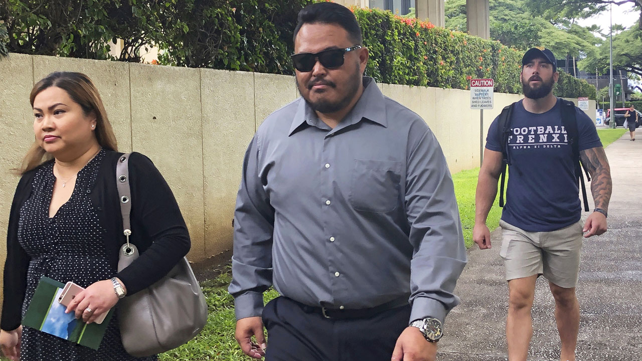 In this Sept. 25, 2019 file photo, former Honolulu police officer Reginald Ramones, center, walks down a street in Honolulu.