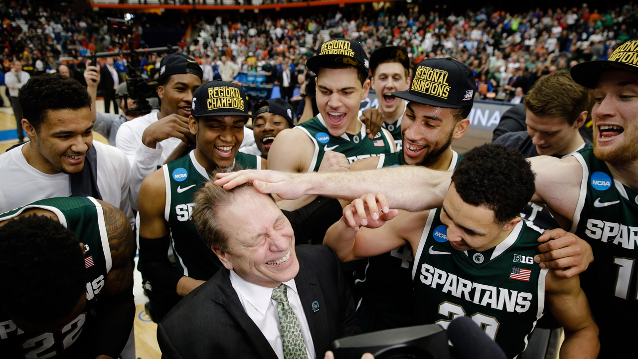 Michigan State head coach Tom Izzo celebrates with his team after the regional final against Louisville in the NCAA men's college basketball tournament Sunday, March 29, 2015.