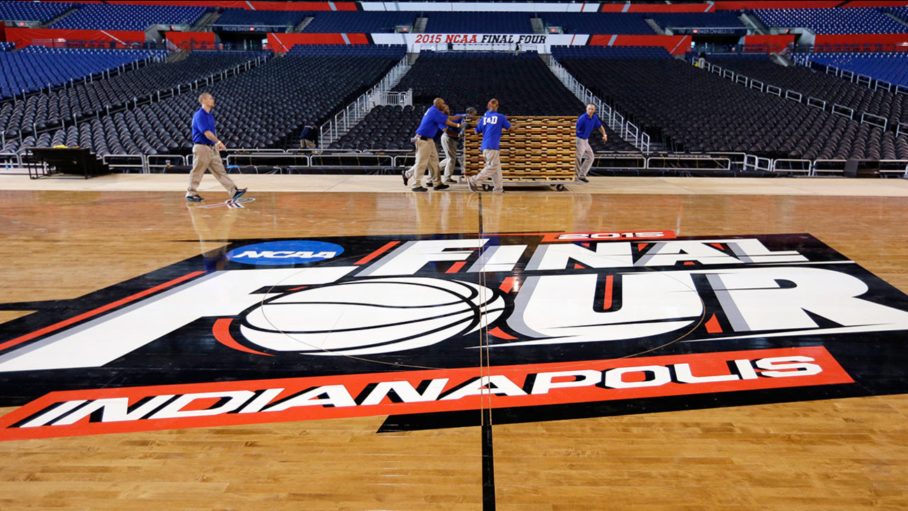 Workers at Lucas Oil Stadium install the court in Indianapolis, Friday, March 27, 2015, as they prepare to host the NCAA Final Four college basketball games on April 4 and 6.