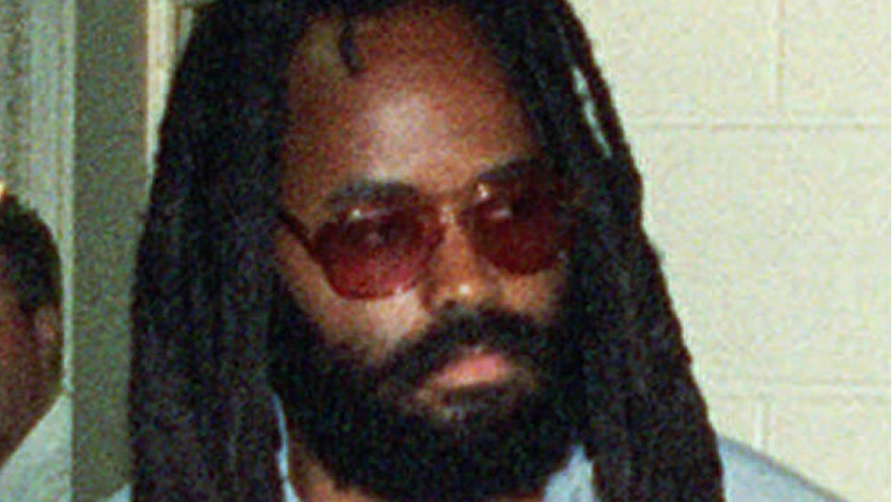 Death row inmate Mumia Abu-Jamal, is lead to court in Philadelphia's City Hall, on July 14, 1995. (AP Photo/POOL, Steven M. Falk)