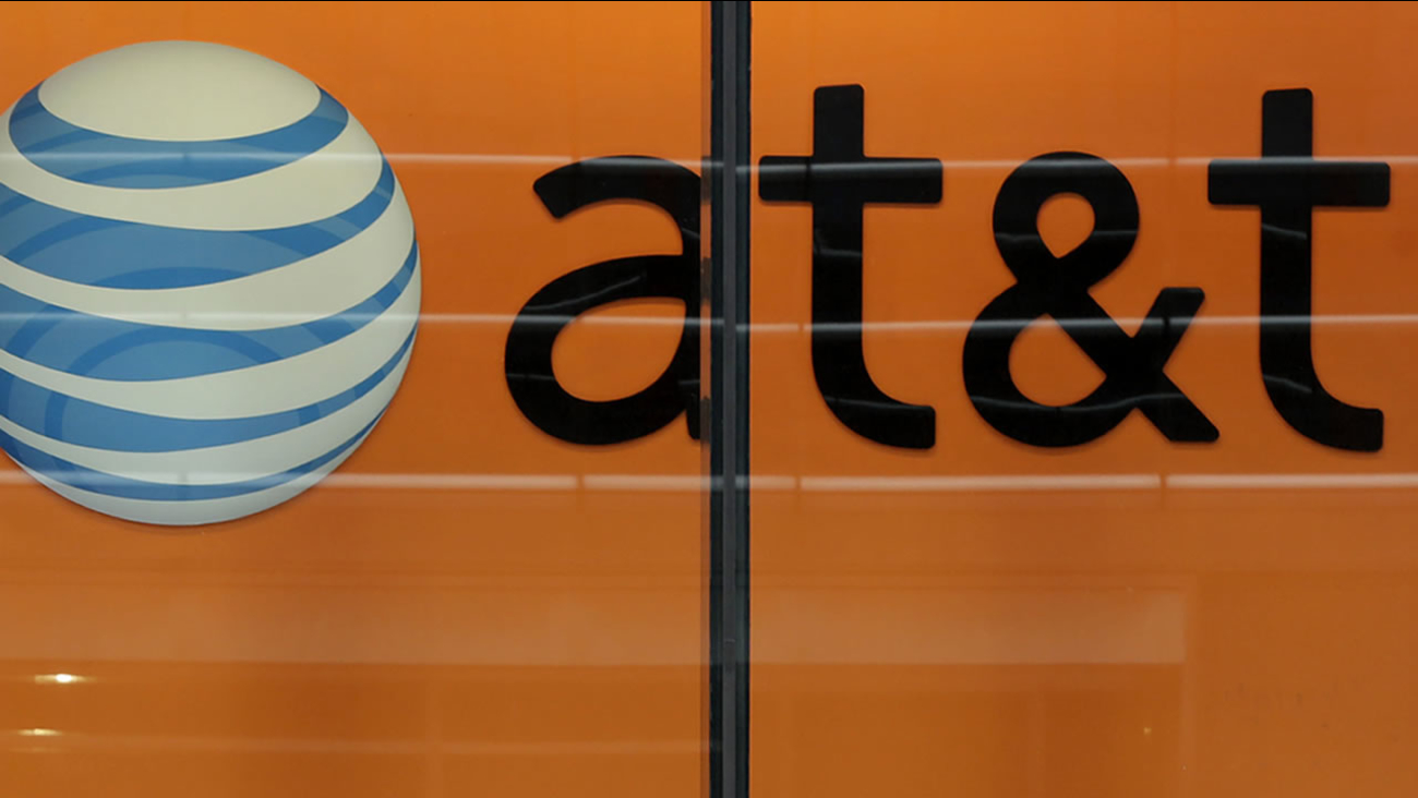 In this Tuesday, Oct. 21, 2014 photo, people pass an AT&T store on New York's Madison Avenue.(AP Photo/Richard Drew)