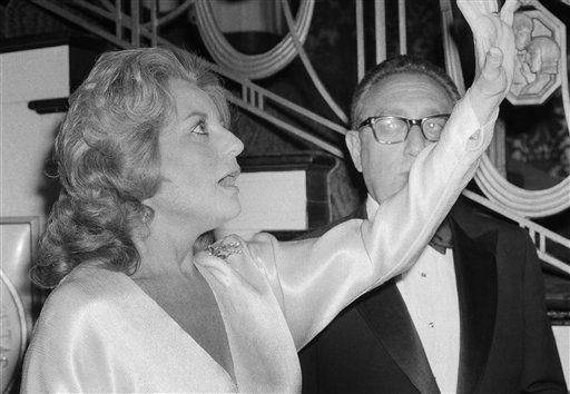 """<div class=""""meta image-caption""""><div class=""""origin-logo origin-image """"><span></span></div><span class=""""caption-text"""">Barbara Walters raises her arm as she reacts to something she sees as she stands next to Dr. Henry Kissinger at a dinner honoring the former secretary of state on May 3, 1980. (AP Photo/ PEC)</span></div>"""