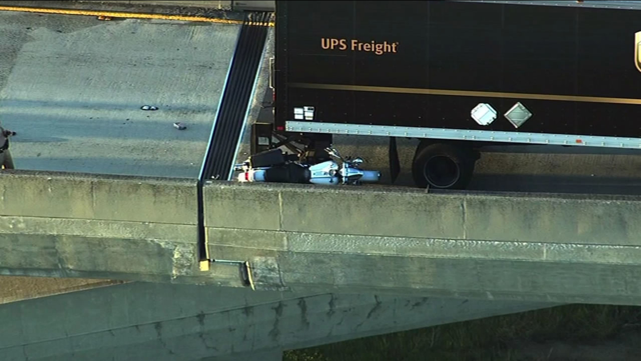 motorcycle wedged between a UPS truck on highway