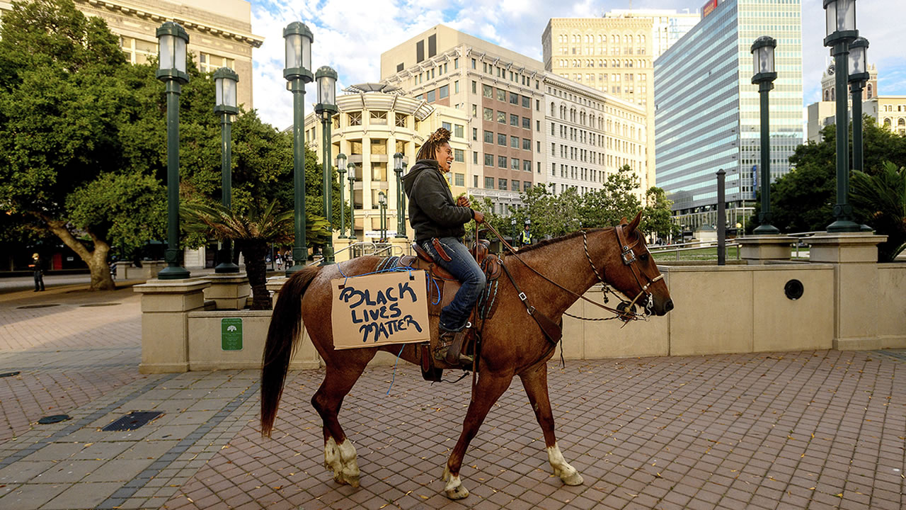 Brianna Noble rides her horse Dapper Dan through downtown Oakland, Calif., Friday, May 29, 2020, to protest the Memorial Day death of George Floyd who died while in police custody in Minneapolis. (AP Photo/Noah Berger)