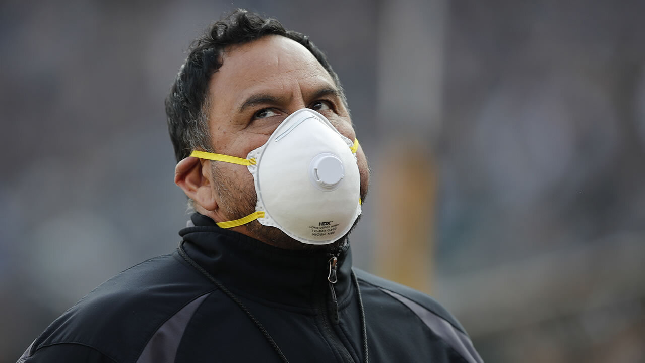 A security guard wears a mask on the field due to wildfires during the second half of an NFL football game between the Oakland Raiders and the Los Angeles Chargers in Oakland, Calif., Sunday, Nov. 11, 2018.