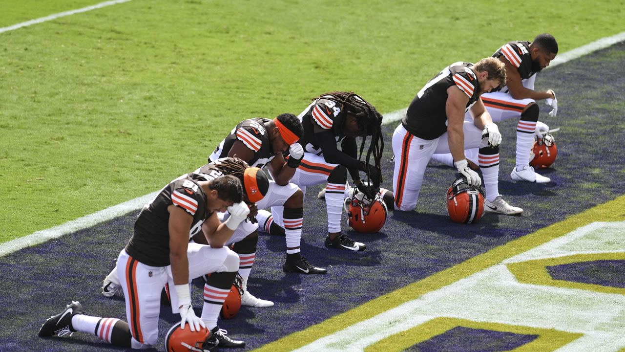 Cleveland Browns players kneel before the play of the National Anthem during an NFL football game against the Baltimore Ravens, Sunday, Sept. 13, 2020, in Baltimore.
