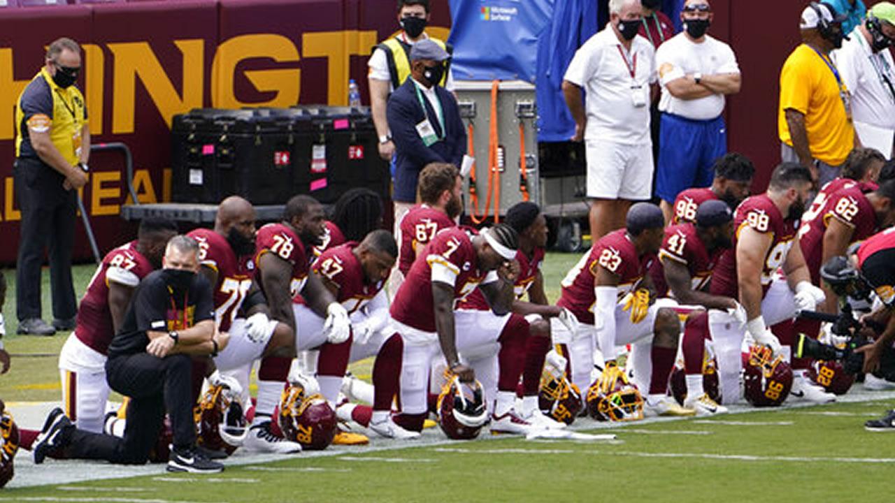 Washington Football Team quarterback Dwayne Haskins (7) and others kneel on the sideline before the start of an NFL football game against the Philadelphia Eagles, Sunday, Sept. 13, 2020, in Landover, Md.