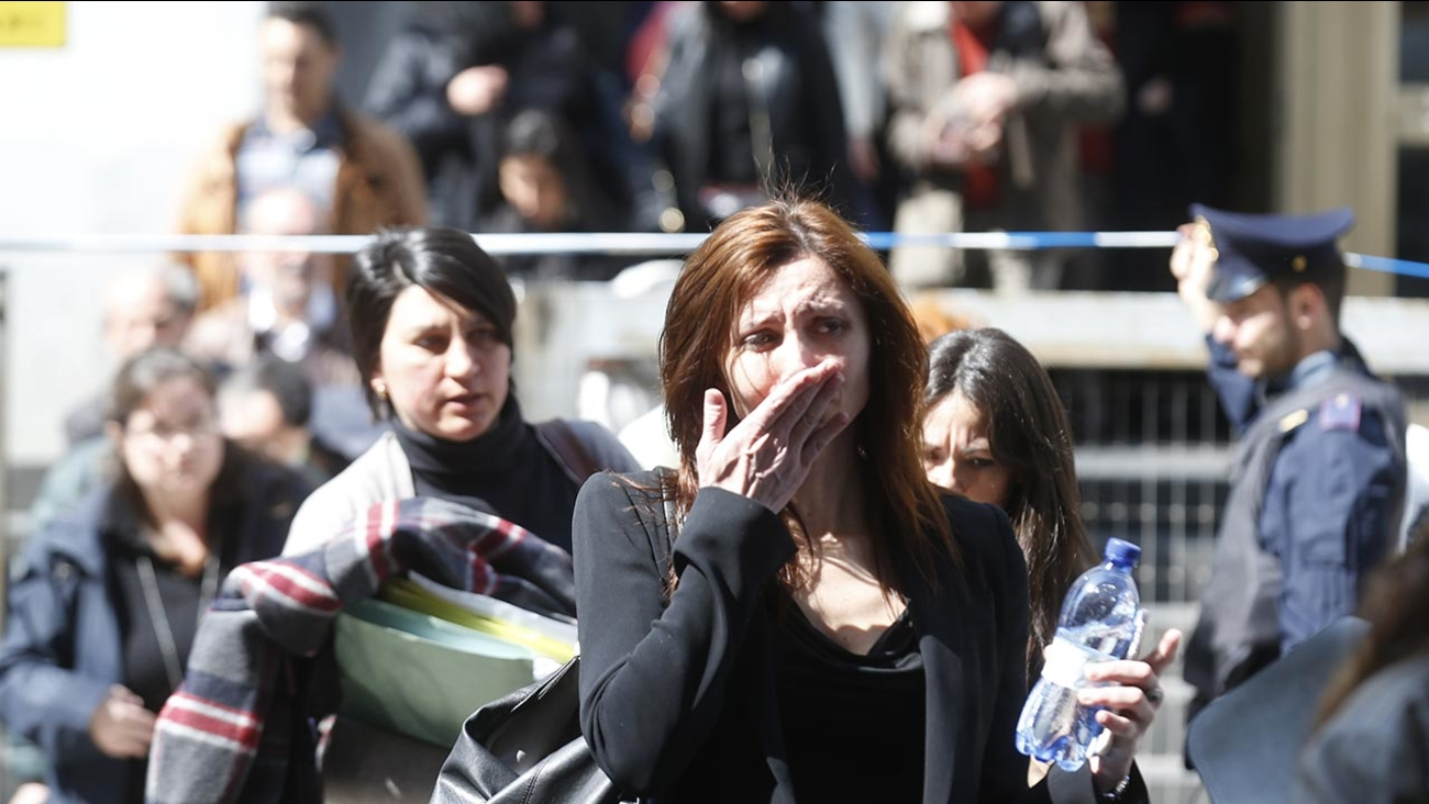 A woman cries as she is evacuated from the tribunal building in Milan, Italy, after a shooting was reported inside a courtroom Thursday, April 9, 2015.