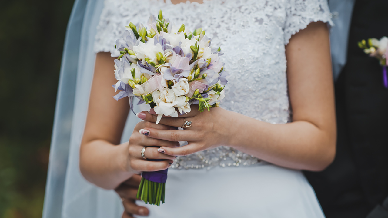 A bride holds a bunch of flowers in this stock photo.