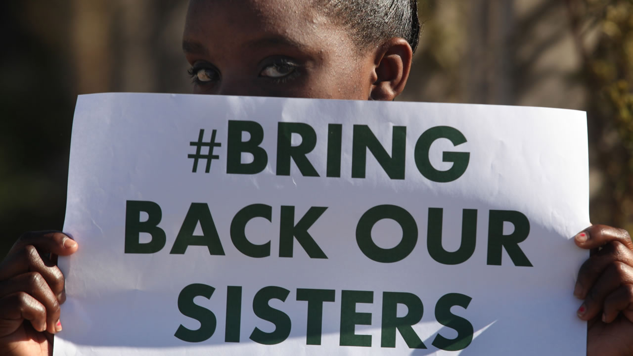A girl from a Soweto school displays a poster in reference to the school girls who were kidnapped from a school in Nigeria, by the Muslim extremist group Boko Haram, Wednesday, May 14, 2014 (AP)