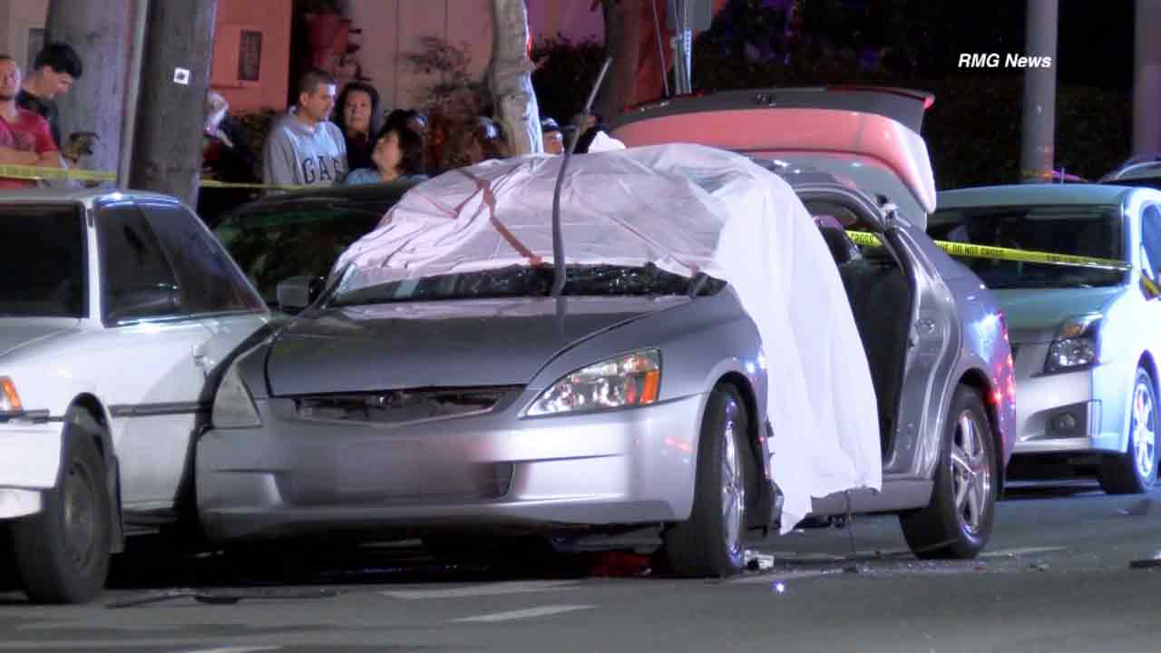 A sheet drapes a car involved in a fatal crash near Collins Street and Reseda Boulevard in Tarzana on Sunday, April 12, 2015.