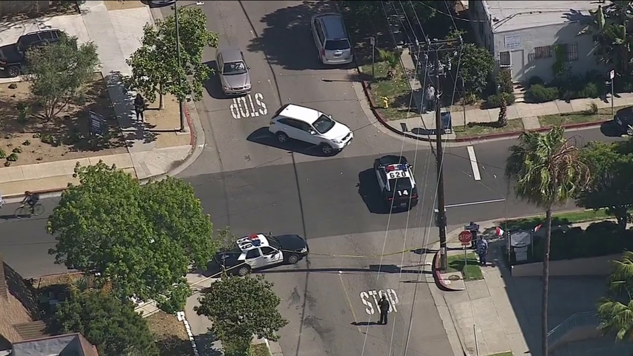 Los Angeles police respond to the scene of a fatal shooting near Woodbine Street and Mentone Avenue in the Palms neighborhood of Los Angeles Thursday, April 16, 2015.