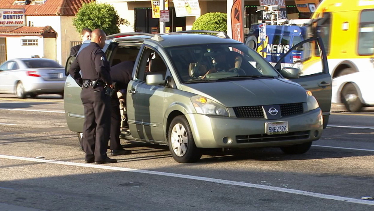 Los Angeles police investigate a car-to-car shooting in South Los Angeles on Sunday, April 19, 2015.