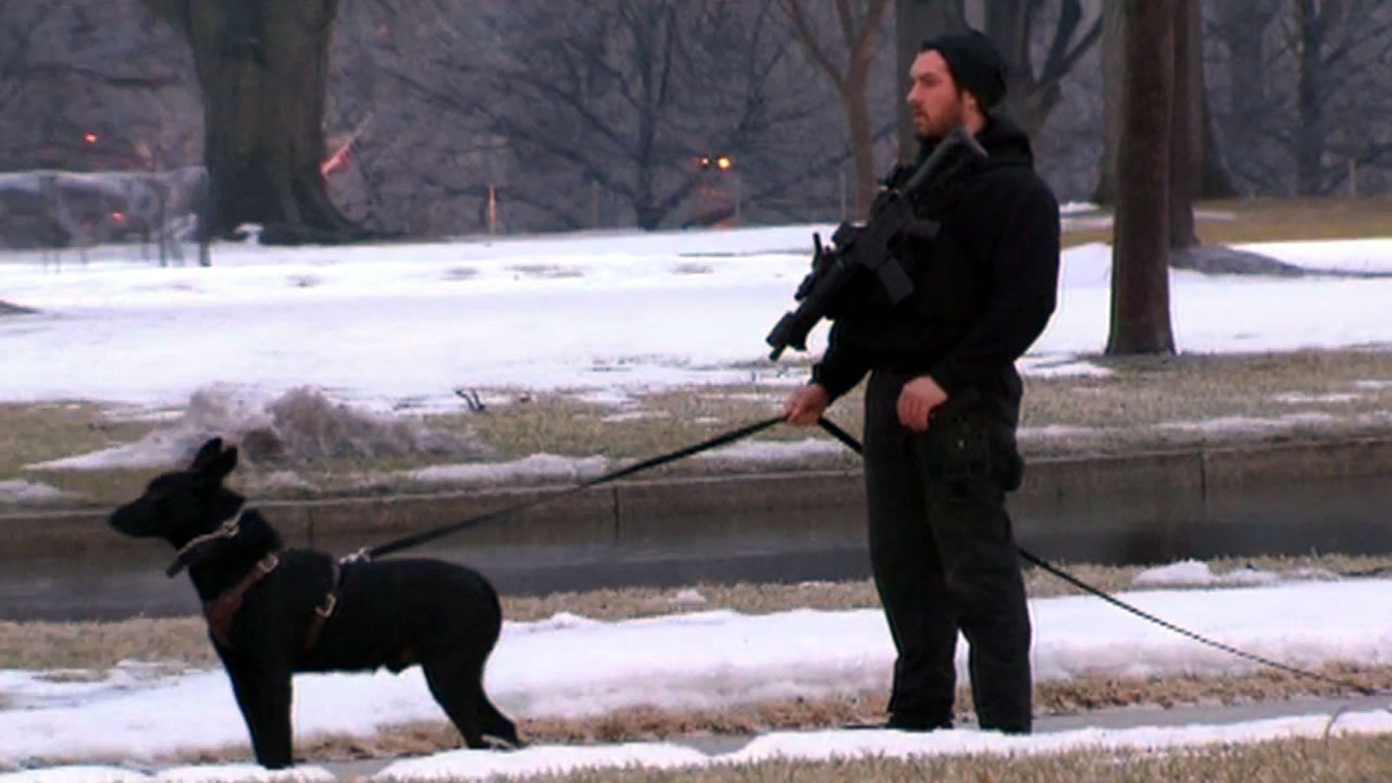 A guard stands watch with a police K-9 outside the White House in Washington on April 19, 2015.
