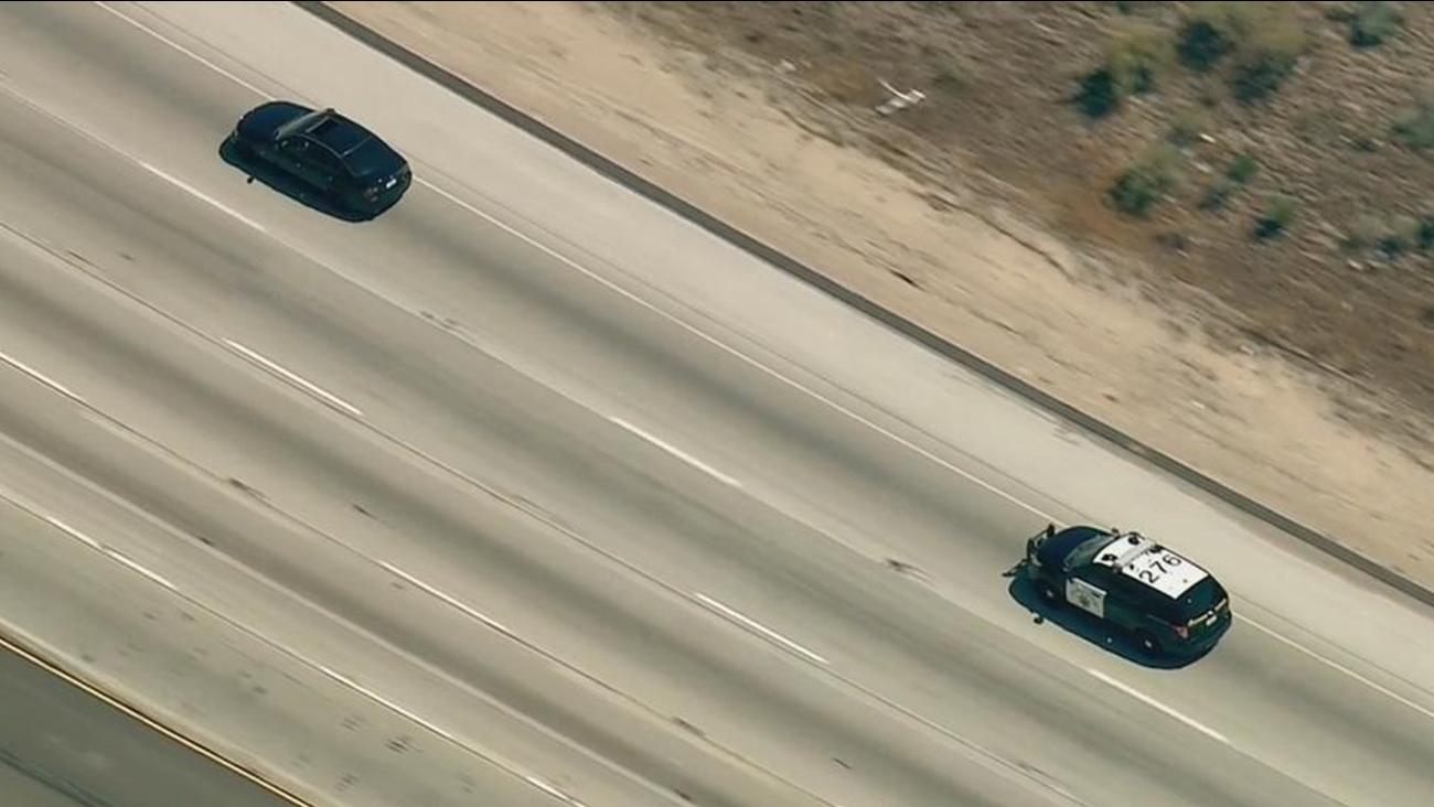 California Highway Patrol officers pursue a suspect in a stolen black BMW on the northbound 15 Freeway in San Bernardino County.