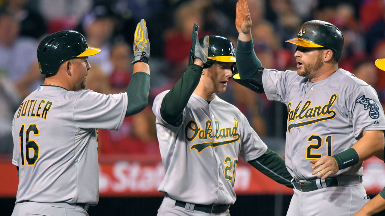 Oakland Athletics' Stephen Vogt, right, is congratulated by Billy Butler, left, and Mark Canha