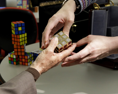 "<div class=""meta image-caption""><div class=""origin-logo origin-image ""><span></span></div><span class=""caption-text"">Erno Rubik, left, the inventor of the Rubik's Cube, reaches out to receive a gold and gemstone version of his cube worth $2.5M. (AP Photo/Julio Cortez)</span></div>"