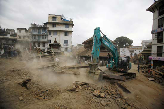 """<div class=""""meta image-caption""""><div class=""""origin-logo origin-image none""""><span>none</span></div><span class=""""caption-text"""">A crane removes debris from the site of a building that collapsed in an earthquake in Kathmandu, Nepal (AP Photo/ Niranjan Shrestha)</span></div>"""