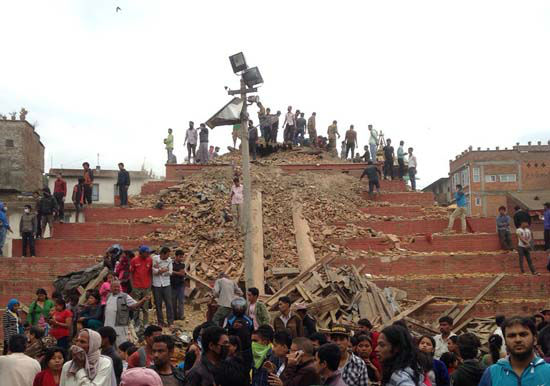 "<div class=""meta image-caption""><div class=""origin-logo origin-image none""><span>none</span></div><span class=""caption-text"">People stand around damage caused by an earthquake at Durbar Square in Kathmandu, Nepal (AP Photo/ Niranjan Shrestha)</span></div>"
