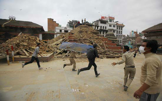 """<div class=""""meta image-caption""""><div class=""""origin-logo origin-image none""""><span>none</span></div><span class=""""caption-text"""">Volunteers run with a stretcher to carry a dead body recovered from the debris of a building that collapsed (AP Photo/ Niranjan Shrestha)</span></div>"""