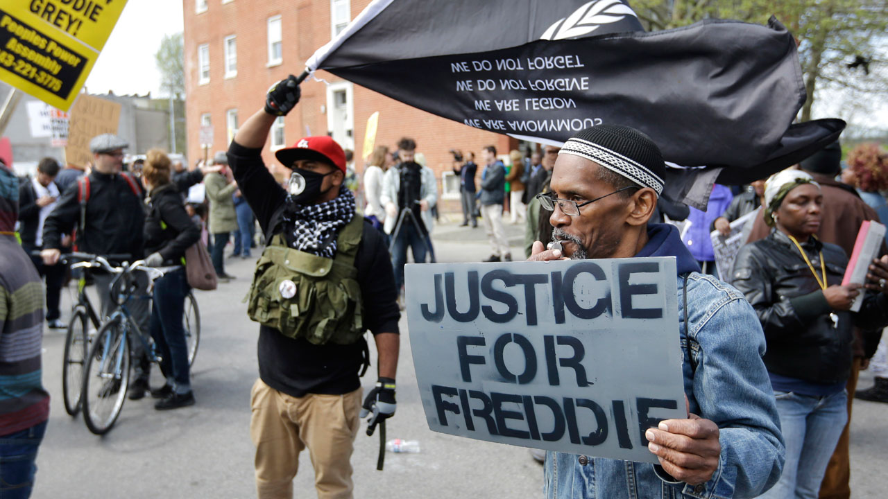 Protestors gather outside the Baltimore Police Department's Western District police station before a match for Freddie Gray, Saturday, April 25, 2015, in Baltimore.