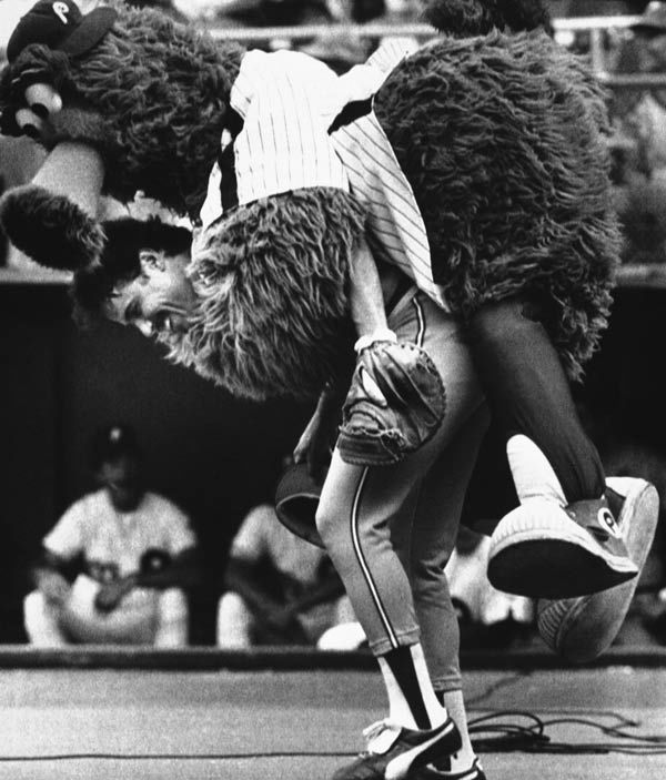"<div class='meta'><div class='origin-logo' data-origin='none'></div><span class='caption-text' data-credit='AP Photo/ Rusty Kennedy'>The ""Phillie Phanatic"" jumps on the back of Atlanta Braves catcher Biff Pocoroba during a pre-game warmup before double header at night on Tuesday, July 12, 1983 in Philadelphia.</span></div>"