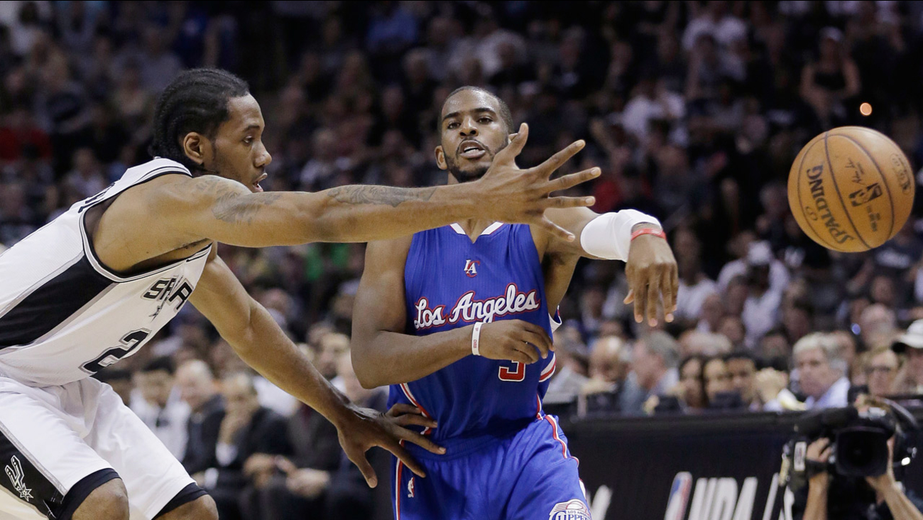 Los Angeles Clippers' Chris Paul passes the ball around San Antonio Spurs' Kawhi Leonard during Game 4 of NBA basketball playoff series, Sunday, April 26, 2015, in San Antonio.