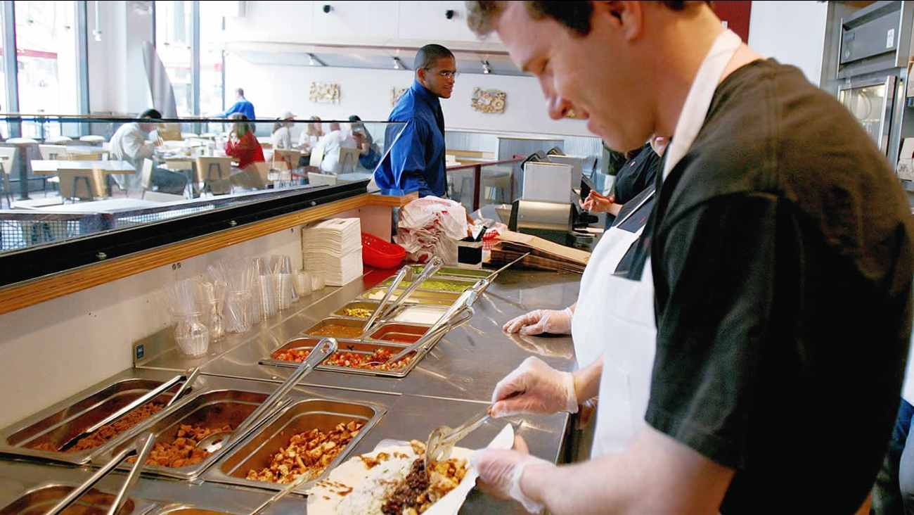 Chipotle manager Ryan O'Toole piles on the ingredients on a chicken burritio, Chipotle's most popular item, at a downtown Denver location on Monday, May 8, 2006. (AP Photo)